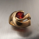 Oregon Sunstone; Red Sunstone bezel set in a hand carved yellow gold setting